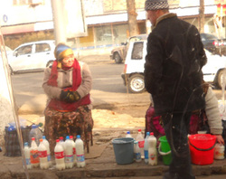 Ms. Zulaikho sells milk from her own cows to a customer in 